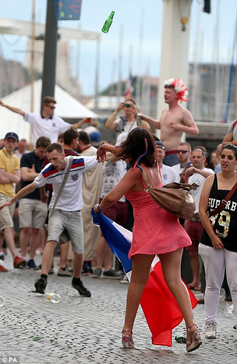 A French woman hurls a beer bottle at English fans after it is believed they tried to yank her flag away on the streets of Marseille