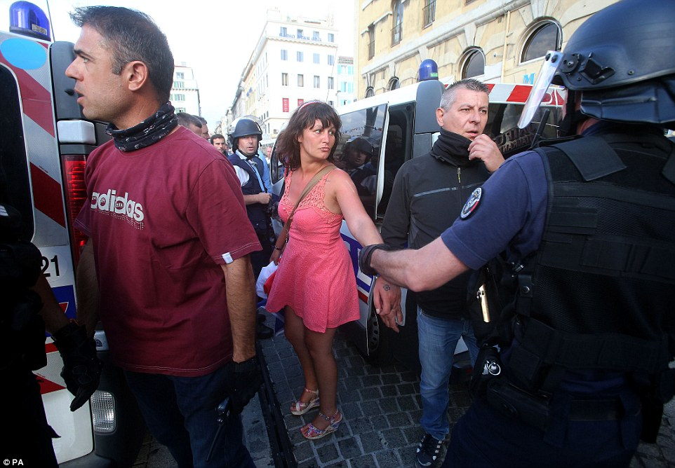 The French woman is arrested by riot police after she threw the bottle as fans clashed with other supporters and police in Marseille