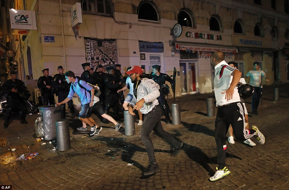 Local youths flee as they are chased through Marseille's Old Port district by English supporters as trouble waged into the night