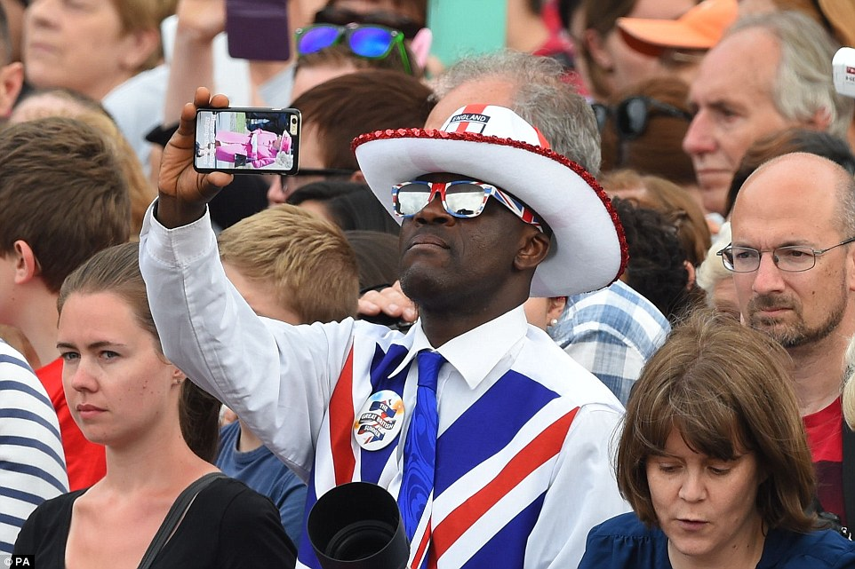 Picture perfect: One enthusiastic Brit waits for the right moment to get some snaps of the Queen as the parade continues down the Mall