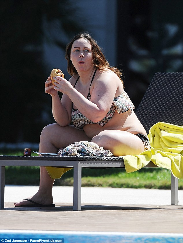 Take a bite: The yo-yo dieter showed off her curves as she perched on the end of a sun-lounger in a patterned bikini and chowed down on the burger
