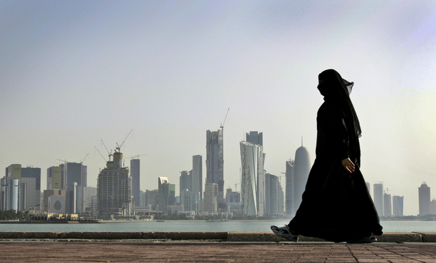A Dutch woman claims she was arrested by Qatari police after reporting that she had been raped. Pictured, a Qatari woman walks in front of the city skyline in Doha (stock image)