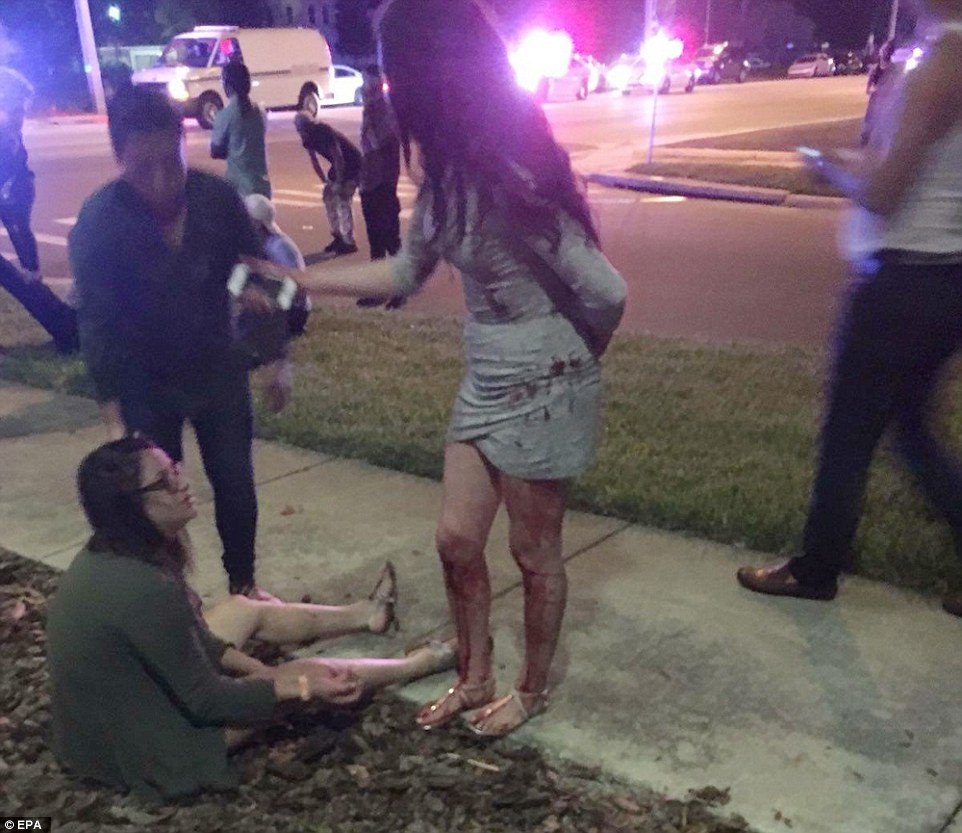 Attack: A woman sits on the ground outside the club while another party-goer, whose legs are covered in blood, stands beside her