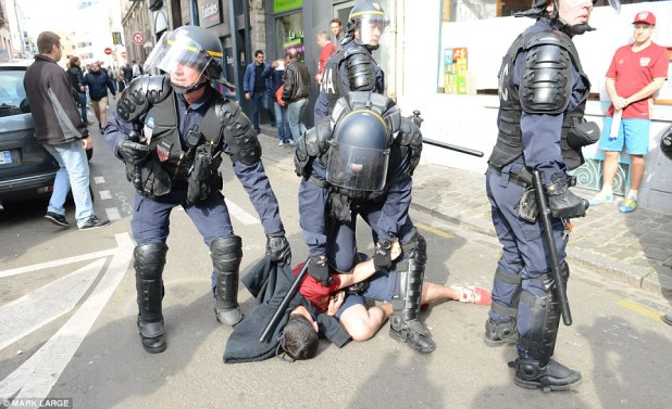 Arrest: One Russian fan could be seen being held down on the ground as riot police descended on the scene in Lille this afternoon