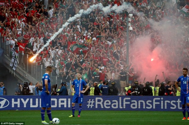 Hungary's supporters throw flares as they celebrate their team's goal during the Euro 2016 group F football match against Iceland today