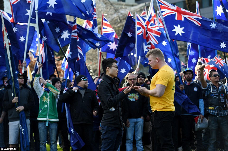 Leader of the United Patriots Front Blair Cottrell (pictured right in yellow) spoke to Vietnamese Australian Steve (pictured centre) who wanted to march at the front of the protesters