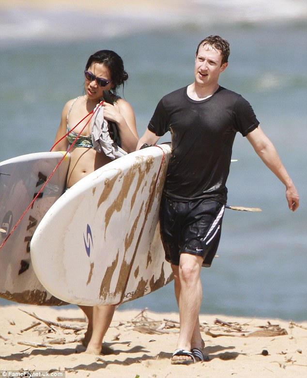 Facebook creator Mark Zuckerberg and his wife Priscilla head back onto the sand after enjoying an afternoon of surfing in Kauai, Hawaii in 2013