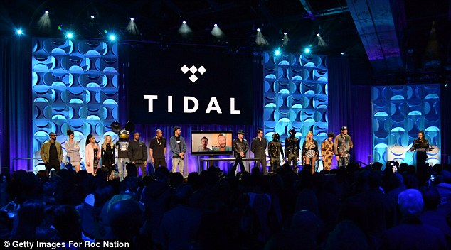 Apple is in talks to buy Jay Z's music streaming service Tidal, a report has claimed. Pictured, Usher, Rihanna, Nicki Minaj, Madonna, Dead Mouse, Kanye West, Jay Z, Jason Aldean, Jack White, Daft Punk, Beyonce and Win Butler at the launch of Tidal last year