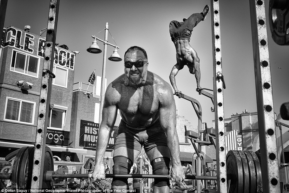Muscle Beach Gym by by Dotan Saguy, who said: 'A weightlifter lifts a barbell loaded with heavy plates while a body builder performs an aerial handstand at the Muscle Beach Gym in Venice Beach, CA'