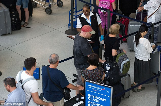 Security increases for the holiday weekend: A Transportation Security Administration employee checks passenger tickets as they get into the security line at JFK