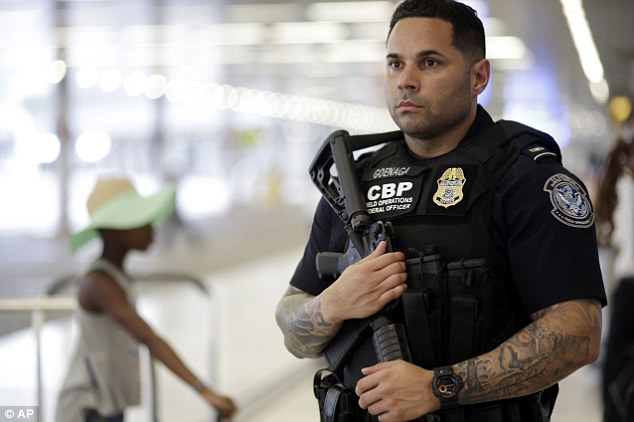 On alert: A U.S. Customs and Border Protection officer patrols outside of the departures area at Miami International Airport