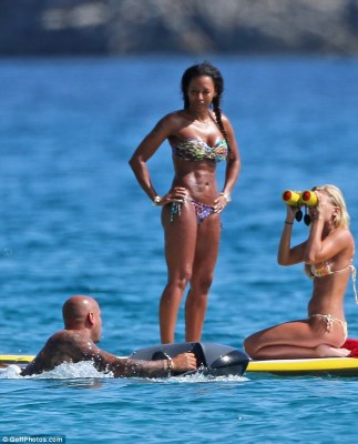 Bikini babe: She unveiled her enviable six pack as she splashed about with husband Stephen Belafonte (left)