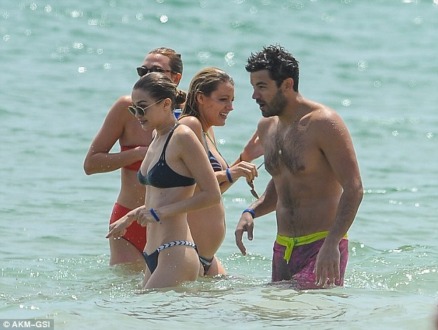Model curves: The 21-year-old model showcased her perfect 10 figure in a clingy black bikini as she splashed around the surf with the famous guests who included pregnant Blake Lively