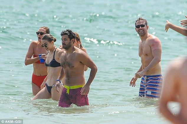 Wading to shore: Gigi made the trek back to the beach while Ryan Reynolds, right, showcased his muscly torso in striped swim trunks
