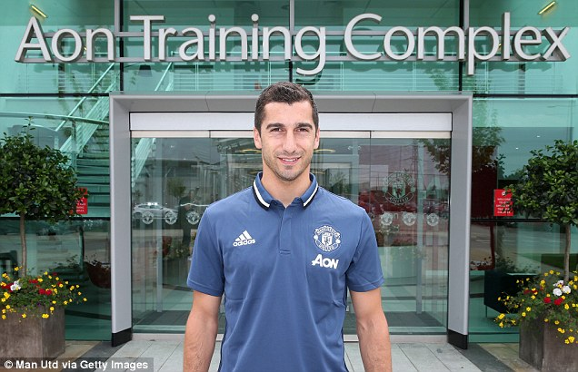 Mkhitaryan poses for a photo outside the club's Aon Training Complex after completing his £26m move