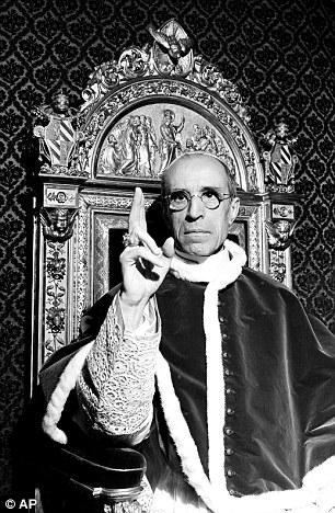 Pope Pius XII, wearing the ring of St. Peter, raises his right hand in a papal blessing as he sits upon his throne at the Vatican in September 1945
