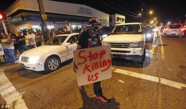 'Stop killing us':Some held placards calling police 'murderers' and pleading for justice after Sterling's death on Tuesday morning