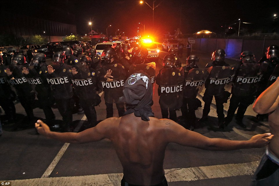 A protester raises him arms in front of a police blockade as marchers take to the streets to demonstrate against the recent fatal shootings of black men by police