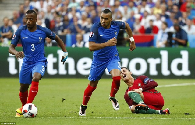 Hurt: Patrice Evra brings the ball away alongside his team-mateDimitri Payet after Ronaldo suffers an injury to his knee 25 minutes in