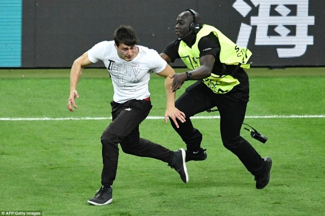 A steward tries to stop a pitch invader during the Euro 2016 final football match between Portugal and France at the Stade de France