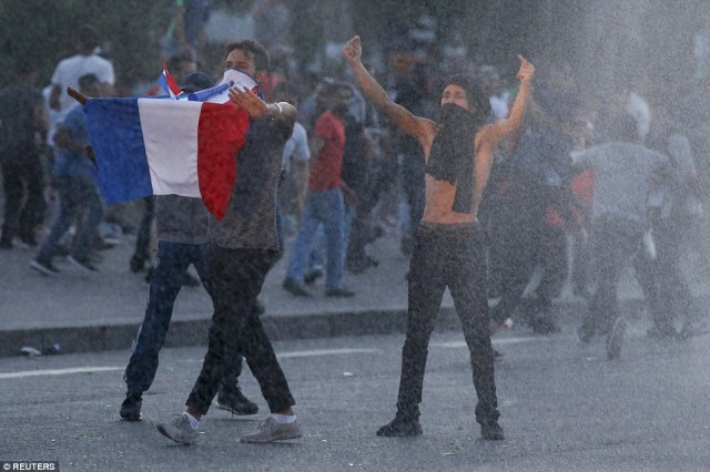 Youths taunt French riot police during clashes near the Eiffel Tower at the Paris fan zone where tens of thousands of people have gathered