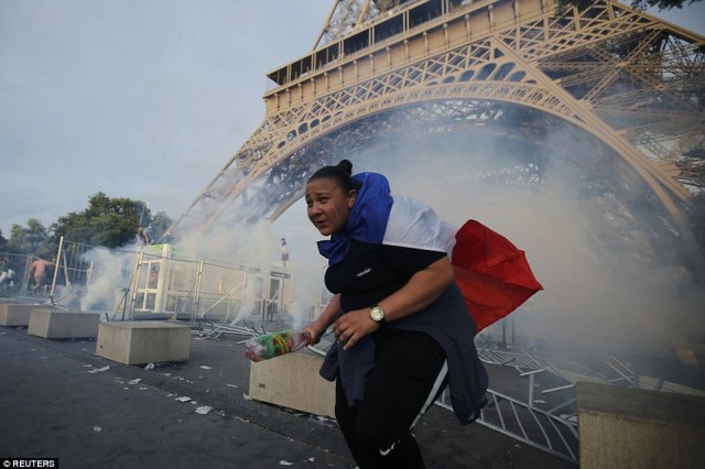 Tear gas floats in the air near the Eiffel Tower close to the Paris fans zone before the start of the game between Portugal and France