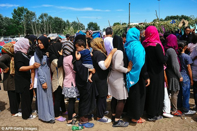 Afraid: Women queue to receive food at a migrant and refugee camp situated on the Serbia-Hungary border in Horgos on July 8 2016