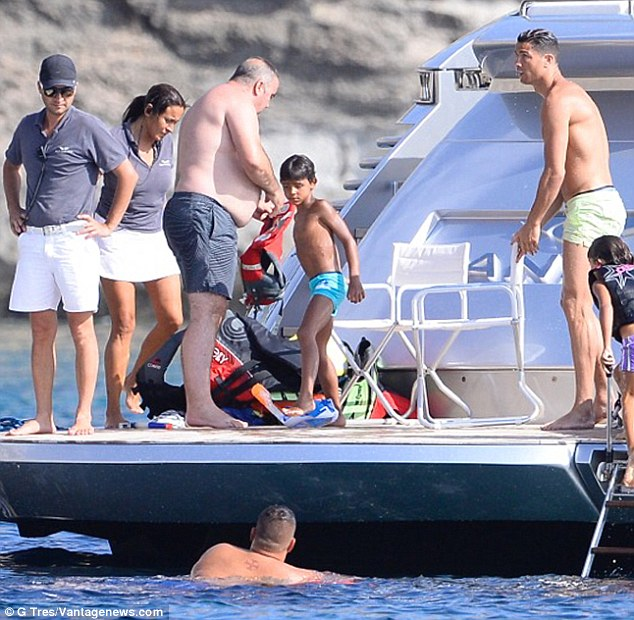 Having fun: Cristiano Jr, five, wore turquoise swimshorts as he played among his family