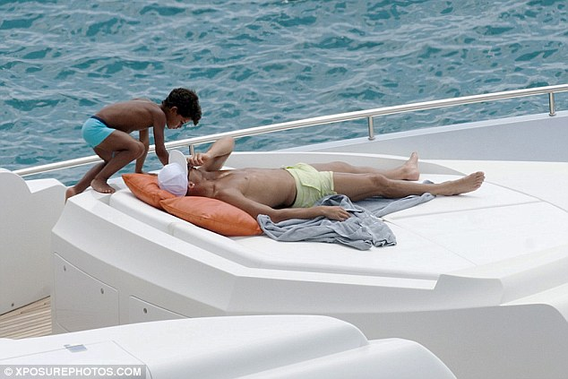 Playful: Cristiano Jr climbed up onto where Cristiano was laying on the deck