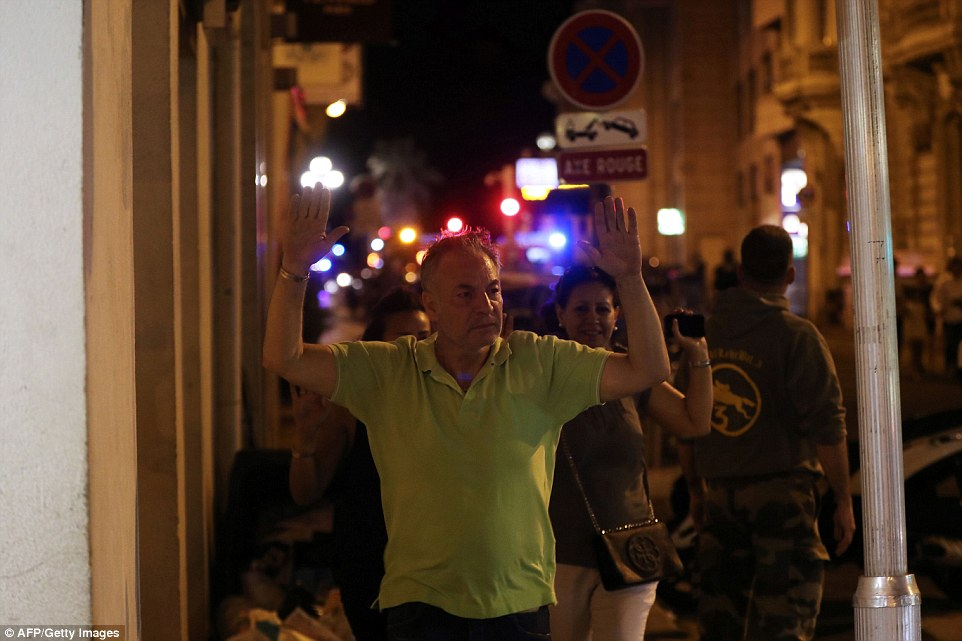 People leaving the area were ordered to hold their hands up as they evacuated the scene near the sea front in Nice last night