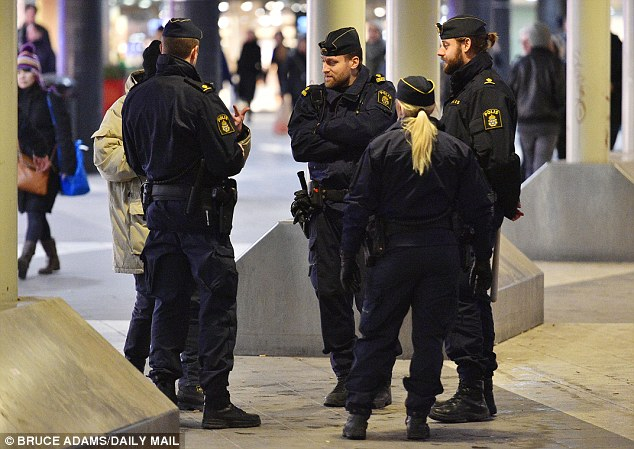 Swedish police check IDs and question men in Stockholm Central Station where  a crowd of far right extremists attacked passers by earlier this year
