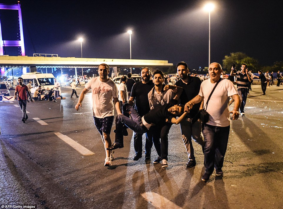 Unarmed civilians carried a man believed to have been shot by Turkish troops away from the Bosphorus bridge in Istanbul