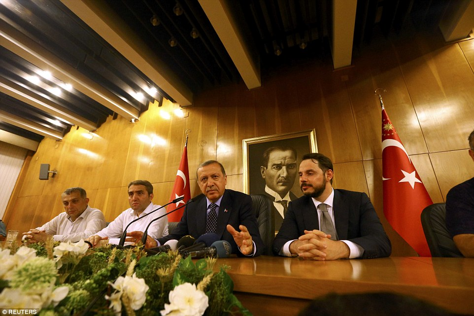 Erdogan, pictured center, said he was going to 'cleanse the military' accusing those soldiers involved in the coup of 'treason'