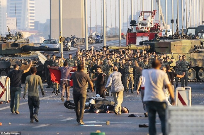 Army personnel who had earlier blocked off Istanbul's Bosphorus Bridge raise their hands in surrender as civilians and police take control