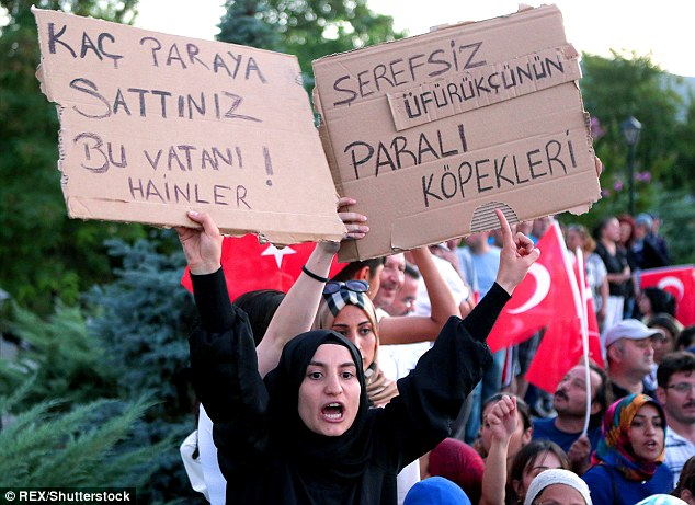 A woman holds up and sign and shouts as the alleged coup members are led into the courthouse near Marmaris