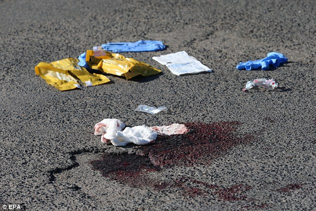 A stain of blood and the remains of a bandage lie on the pavement close to where the axe attack happened in Germany