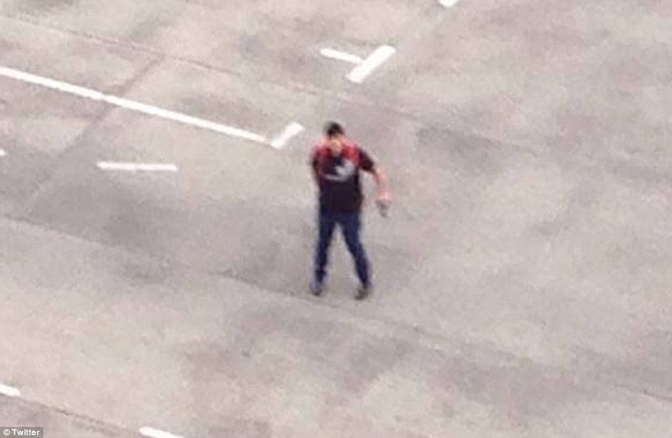 Pictured is the shooter on the car park roof of the shopping centre in Munich. The city is now in lockdown as police hunt the killer