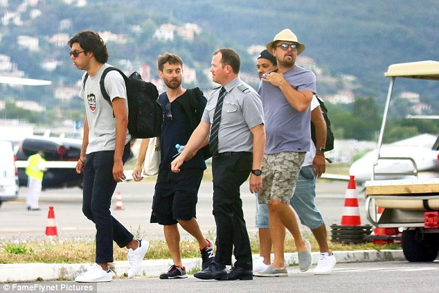 DiCaprio was pictured donning a pair of camouflage shorts, a purple T Shirt and a straw hat as he made his way across the tarmac in the heat with friends Tobey Maguire (second from left) and Vincent Laresca (left)