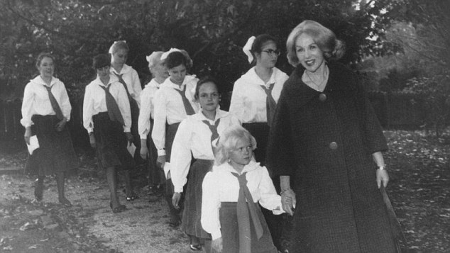 Anne Hamilton-Byrne pictured here with some of the children - holding hands with one of the bleach-blonde children