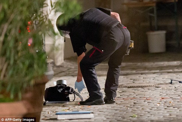 A polic officer in protective gear inspects a back pack used to carry an explosive device at the scene of a suicide attack in the southern German city of Ansbach