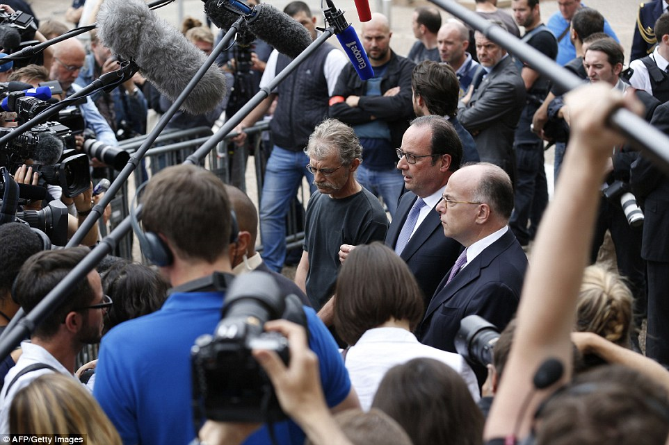 French President Francois Hollande (centre) flanked by Hubert Wulfranc mayor of Saint-Etienne-du-Rouvray (left) and French Interior Minister Bernard Cazeneuve (right), speaks to the press as he leaves the Saint-Etienne-du-Rouvray's city hall