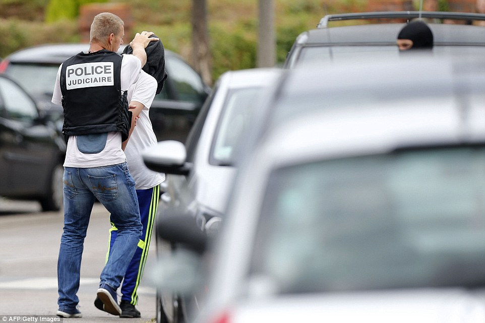 Arrest: The man was pictured being bundled into a police car after a raid on a house in the town of Saint-Etienne-du-Rouvray