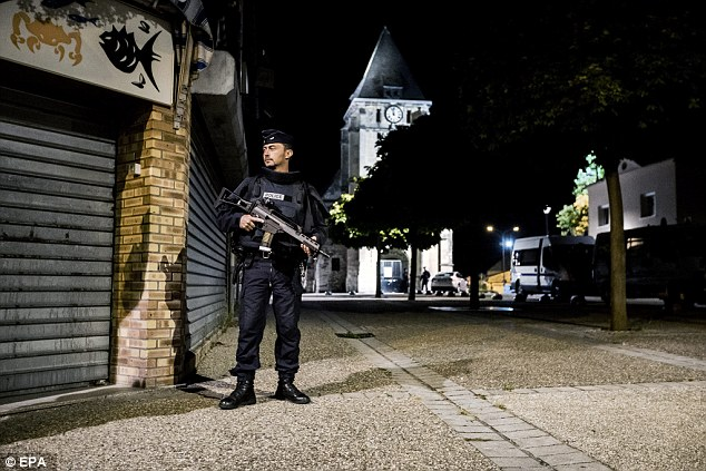 French riot police guard the street on Tuesday night that leads to the church in Saint-Etienne-du-Rouvray where a fatal hostage taking incident happened, near Rouen