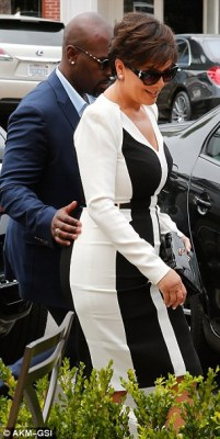 Doing his job: Meanwhile, Kris Jenner, 60, paid a visit to her mom MJ's new store in San Diego accompanied by toyboy and bodyguard Corey Gamble, 35, who placed a protective arm around her as they walked
