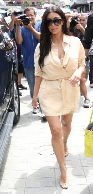 Center of attention: Kim Kardashian, 35, stepped out in San Diego Wednesday in a beige wraparound shirt dress tied at the waist that showed off her newly trim figure after losing all her pregnancy pounds