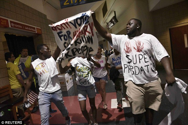 Protesters walk through the halls of the Wells Fargo Center with a banner reading: 'Don't vote for Hillary. She killin [sic] blk [sik] people'