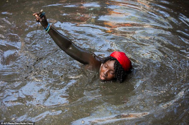 A pilgrim takes a bath in a sacred mud pool during the annual Voodoo celebration in Plaine-du-Nord, Haiti