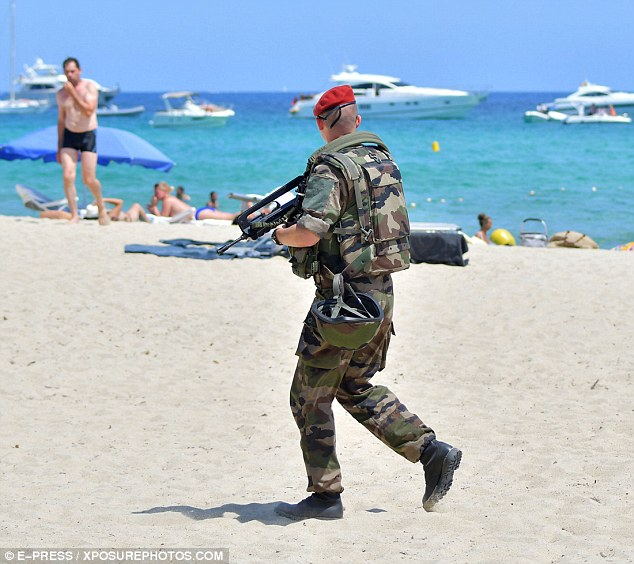 A police looks out towards sun-worshippers and the pristine blue sea of the Cote d'Azur as he patrols the beach