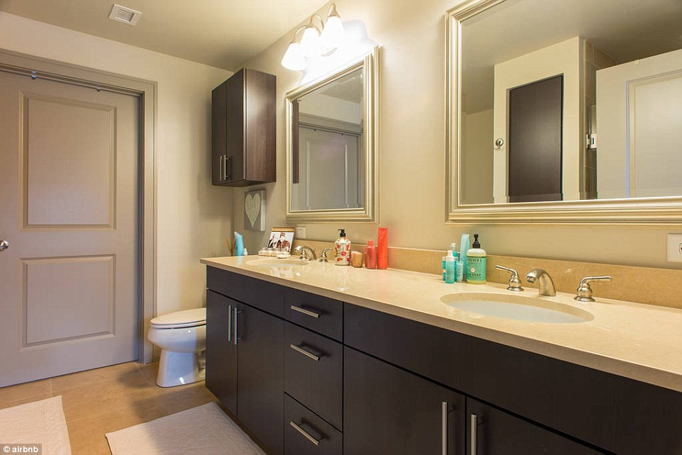 The couple's spacious bathroom is designed with two sinks for both occupants and has plenty of lighting for doing makeup or personal grooming