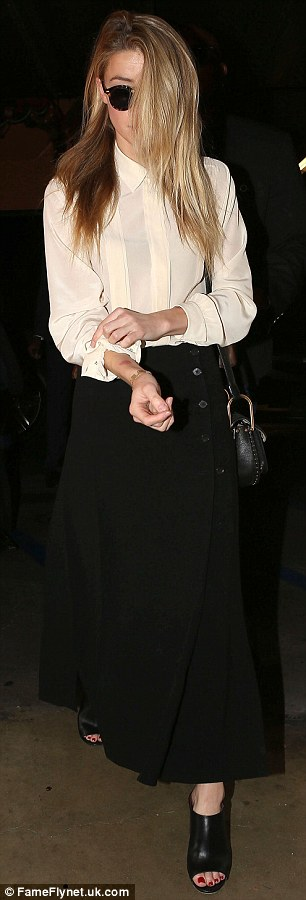 Dressing down: She wore a white blouse buttoned up to her neck, an ankle-length black skirt and peep-toe shoes for the deposition